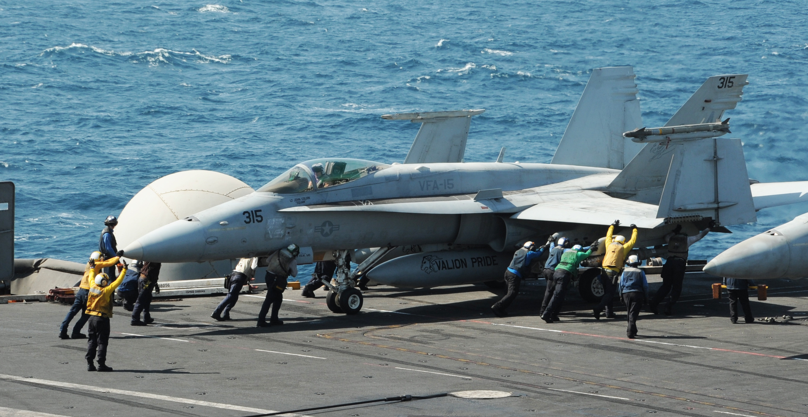 140808-N-MU440-073  ARABIAN GULF (Aug. 8, 2014) Sailors guide an F/A-18C Hornet assigned to the Valions of Strike Fighter Squadron (VFA) 15 on the flight deck of the aircraft carrier USS George H.W. Bush (CVN 77). George H.W. Bush is supporting maritime security operations and theater security cooperation efforts in the U.S. 5th Fleet area of responsibility. (U.S. Navy photo by Mass Communication Specialist 3rd Class Lorelei Vander Griend/Released)