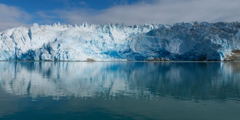 A coastal glacier in southern Greenland mirrored in the sea. Image- Claire Rowland via Flickr