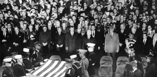 """AR8255-3K                  25 November 1963  Burial and folding of the flag ceremony for President John F. Kennedy.  Photograph includes: (right side, front to back) Jacqueline Kennedy, Robert F. Kennedy, Eunice Shriver, Patricia Lawford, Jean Smith, Super of the Arlington National Cemetery Jack Meltzer, (front row middle to right) President of West Germany Heinrich Luebbe, General Charles de Gaulle of France, Emperor of Ethiopia Haile Selassie, President of the Phillipines Diosdado Macapagal, and mourners. Gravesite, Arlington National Cemetery, Washington, D.C.  Please credit: """"Abbie Rowe. White House Photographs. John F. Kennedy Presidential Library and Museum, Boston"""""""